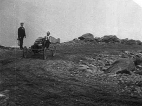 B/W 1905 race car coming around corner in car race on Pike's Peak / documentary