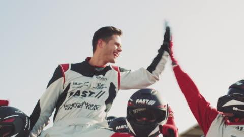 racerförare firar framgången med team - vinna bildbanksvideor och videomaterial från bakom kulisserna