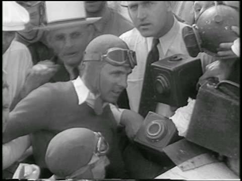 vídeos de stock e filmes b-roll de b/w 1933 race car driver in hat goggles talking into microphones after indianapolis 500 - 1933