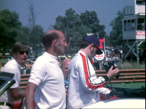 race car driver peter revson stepping over guardrail walking onto racetrack at midohio sports car course / race car driver jackie stewart wearing... - mustang convertible stock videos & royalty-free footage