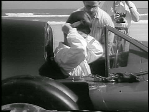 b/w 1935 race car driver sitting in car putting on leather helmet / daytona beach florida - 1935 stock videos & royalty-free footage