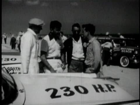 vidéos et rushes de race car drivers fireball roberts, curtis turner and herb thomas standing and talking next to a car / daytona beech, florida, usa / audio - couvre chef