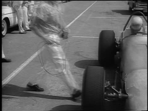 b/w 1965 race car engineers inspecting tires on race car / phoenix international raceway / newsreel - 試運転点の映像素材/bロール