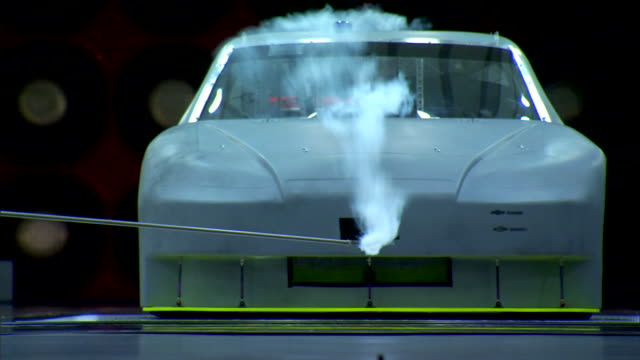 vidéos et rushes de race car in front of red wall of spinning jets in active wind tunnel unidentifiable male hand holding smoke generator probe in front of vehicle white... - essai de voiture