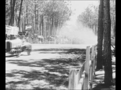 stockvideo's en b-roll-footage met race car skids around turn straightens drives on at french grand prix race / car speeds along straightaway man waves flag at left / race car driver... - 1921