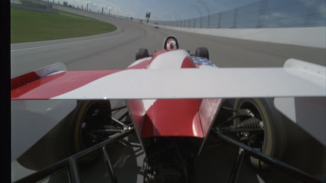 a race car speeds around a track and catches up with its competitor. - 50 seconds or greater stock videos & royalty-free footage
