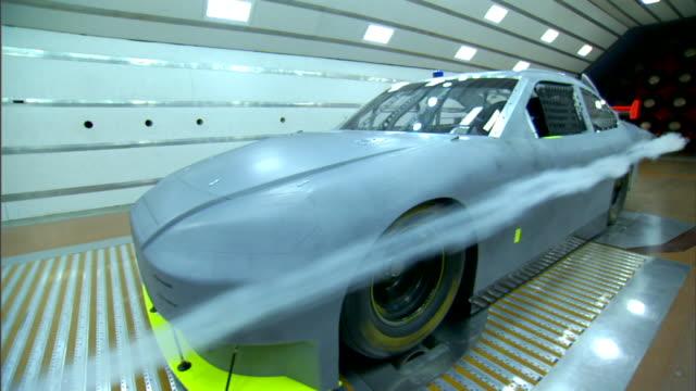 vidéos et rushes de race car viewed from front left corner in active wind tunnel, white smoke originating from left of camera streaming on left side of car & moving over... - essai de voiture