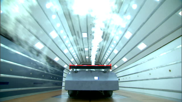 vidéos et rushes de race car viewed from rear in active wind tunnel with white lights on ceiling & brown floor, white smoke streaming over automobile toward camera.... - essai de voiture