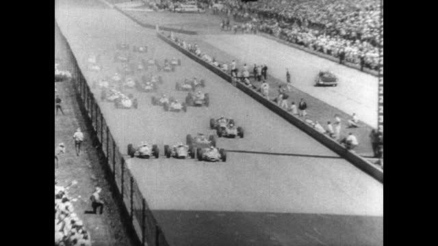 vidéos et rushes de race cars at the starting line of a large racing track / crowd watches from the stands / race begins / one car hits the side wall and tires fly... - graham hill