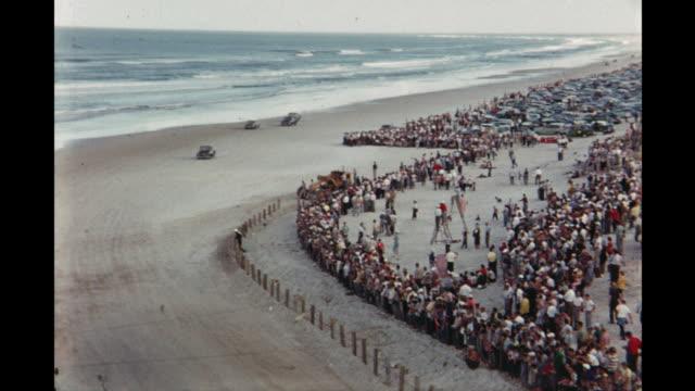 race cars driving on daytona beach florida usa - circuito di daytona video stock e b–roll