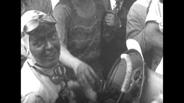 POV 1928 race from grandstand / VS Formula One cars speed around track / CU driver Louis Meyer sitting in car gets encouragement from fans / VS cars...
