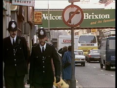 vídeos de stock, filmes e b-roll de story 3 england london brixton ms two white policemen walk along beat young policemen in meeting ext ms police along street in brixton liverpool... - brixton