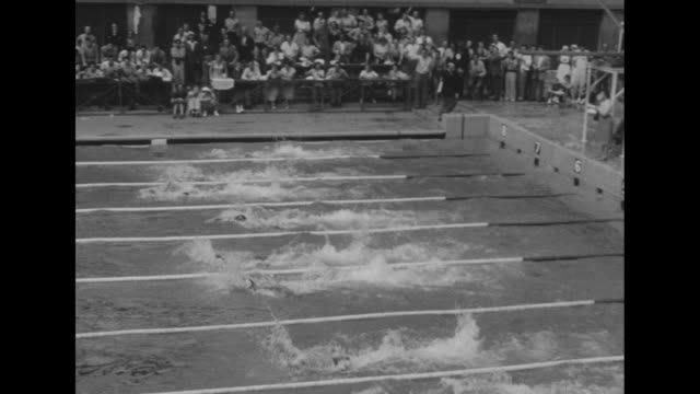 vidéos et rushes de race start at empire pool during summer olympics in london / man with garment over head in summer heat / swimmers approach end of pool / underwater... - en individuel