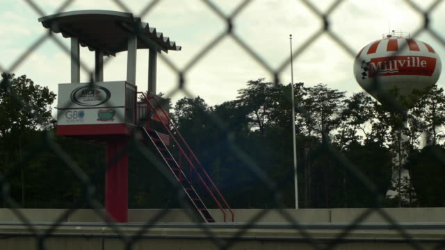 a race track starting tower and round water tower  behind a wire fence. - fence stock-videos und b-roll-filmmaterial