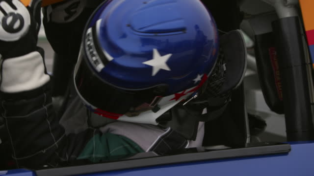 CU TU Racecar driver getting out of racecar and taking off his helmet / Long Pond, Pennsylvania, USA