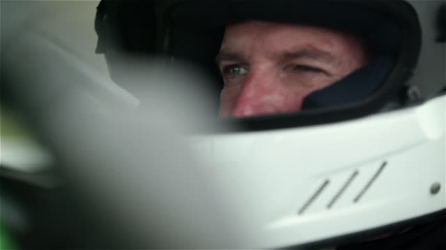 ECU. Racecar driver in white helmet glances at rear view mirror and squints his eyes to focus on the race ahead.