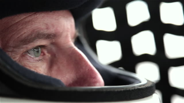 Stock-car driver's eyes check rearview mirror, focus on race
