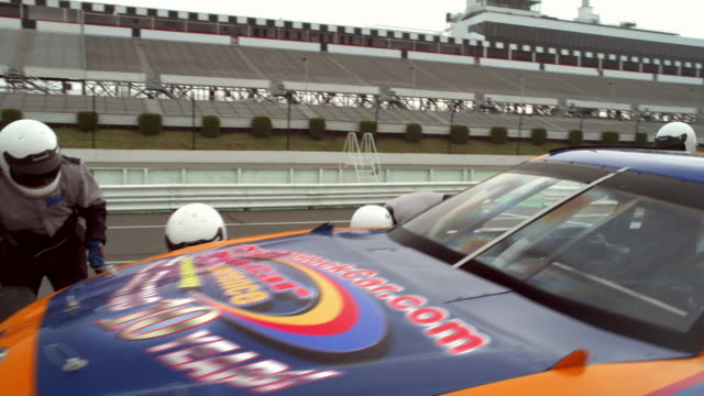 WS ZI MS PAN Racecar pulling into pit stop lane while crew works quickly to service it / Long Pond, Pennsylvania, USA