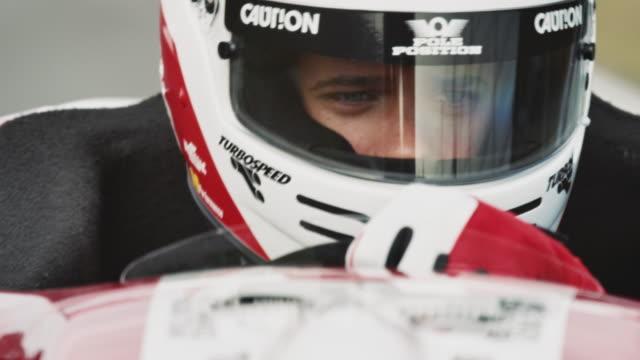 Racedriver in cockpit steering a formula one car