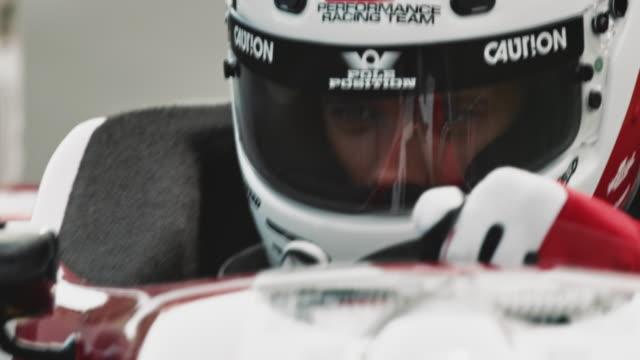 racedriver in cockpit steering a formula one car - automobile da corsa video stock e b–roll