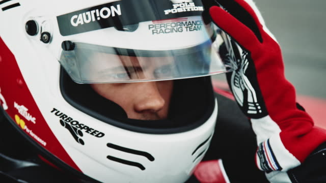 racedriver puts on gloves and closes his visor - casco da motociclista video stock e b–roll