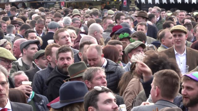 racegoers react as they watch the action from the guinness village at cheltenham racecourse on st patrick's thursday on march 15 2018 in cheltenham... - cheltenham racecourse stock videos and b-roll footage