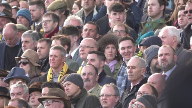Racegoers watch the racing at Cheltenham Racecourse on March 13 2018 in Cheltenham England Thousands of racing enthusiasts are expected at the...