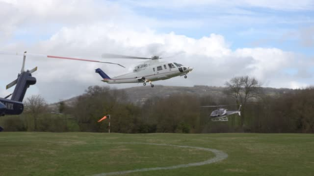 racegoers who have just arrived by helicopter at the helipad near cheltenham racecourse chauffeur driven in bentley cars to the racecourse on march... - cheltenham racecourse stock videos and b-roll footage