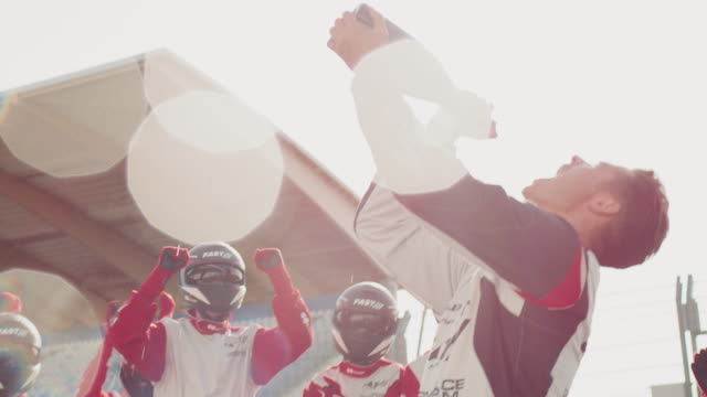 racer and crew members celebrating at sports venue - spraying stock videos & royalty-free footage