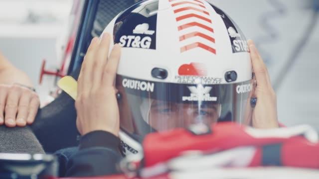 racer anhören trainer während des tragens helm - sturzhelm stock-videos und b-roll-filmmaterial
