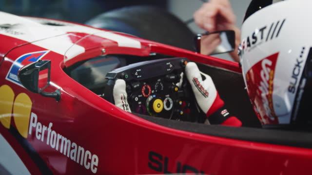 Racer receiving steering wheel from technician