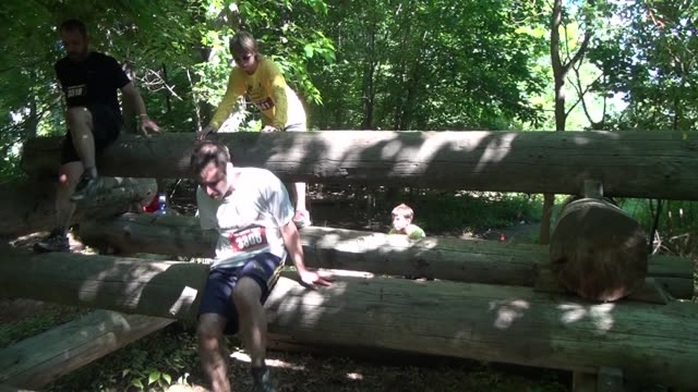 Racers in obstacle and adventure event go over logs and some go under