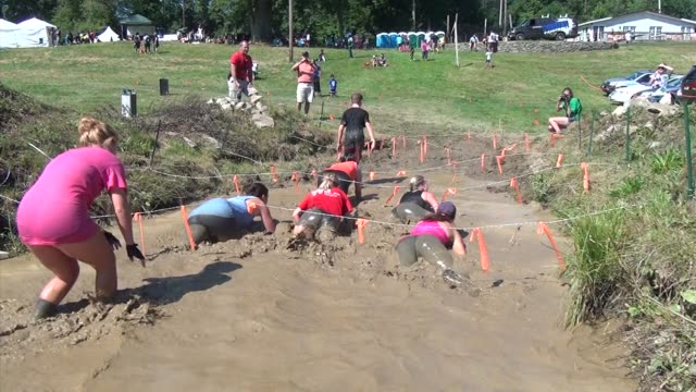 Racers in obstacle and adventure event jump into mud puddle under barbed wireSurvival Race