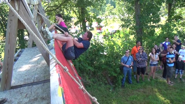 racers in obstacle and adventure event struggle to get over high wall survival race - salmini stock videos and b-roll footage