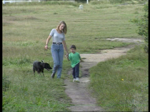 Videofit picture released ITNLIB ENGLAND London Wimbledon EXT LMS 'Jane' with young boy 'Luke' and dog along path towards in reconstruction of crime...