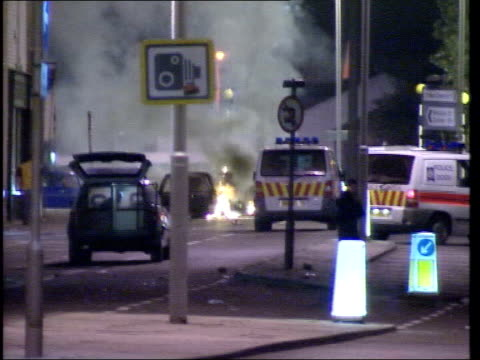 BNP support LIB Lancashire Oldham Police and other vehicles on street as fire seen burning in b/g GV burnt out car lying on side with fire seen...