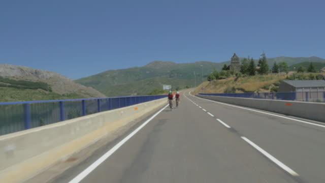 racing bikers riding on a road - 乗物後部から見た視点点の映像素材/bロール