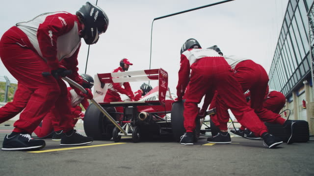 racing crew repairing racecar at pit stop - formula one racing stock videos & royalty-free footage