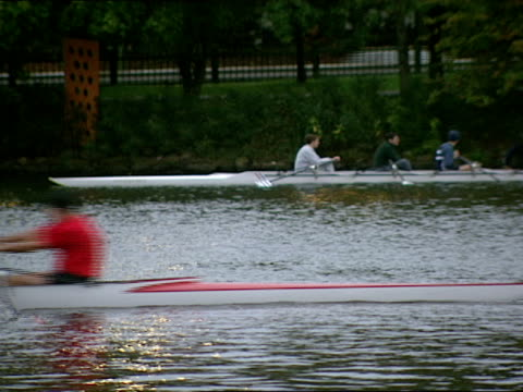 racing crew speeds past a resting crew's shell. - fluss charles stock-videos und b-roll-filmmaterial