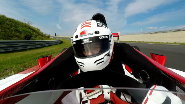 stockvideo's en b-roll-footage met autocoureur in cockpit sturende formule 1 auto - sporthelm