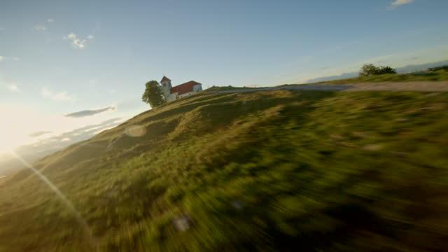 vidéos et rushes de drone de course aérienne volant le long de la route menant à une église sur une colline - drone