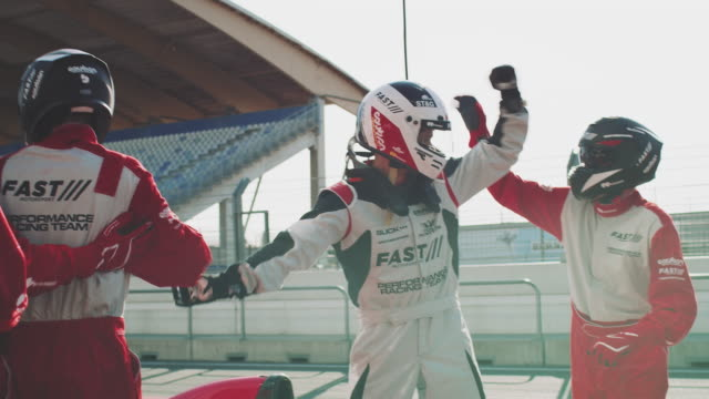 racing team cheering at sports venue - competizione video stock e b–roll