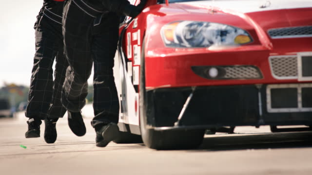 slo mo. racing team pit crew runs and pushes stock car into pit road for repairs. - pushing stock videos and b-roll footage