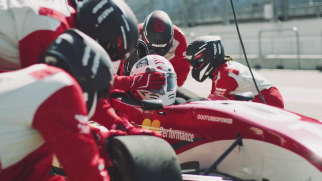racing team repairing formula one car at pit stop - stabilimento sportivo video stock e b–roll