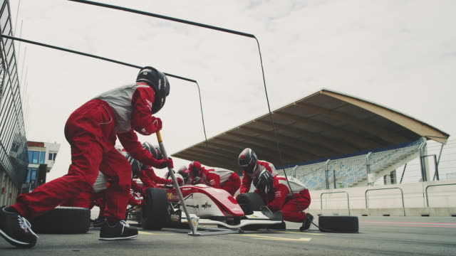 racing team repairing formula one car at pit stop - crash helmet stock videos & royalty-free footage