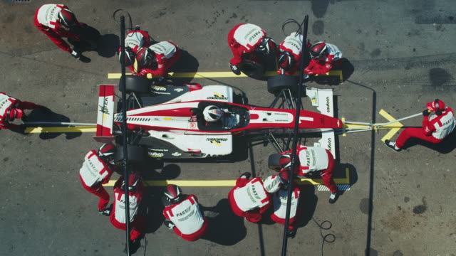 racing team replacing tire of racecar at pit stop - crew stock videos & royalty-free footage