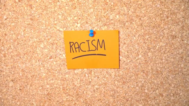 racism word on paper pinning up on corkboard by a man - racism stock videos & royalty-free footage