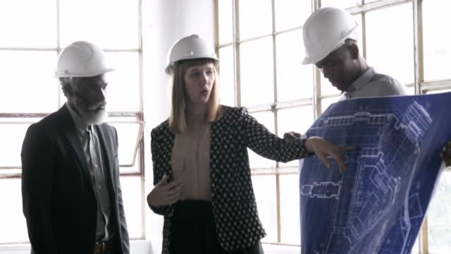 vídeos de stock, filmes e b-roll de rack focus, architects look over blueprints - capacete de trabalho