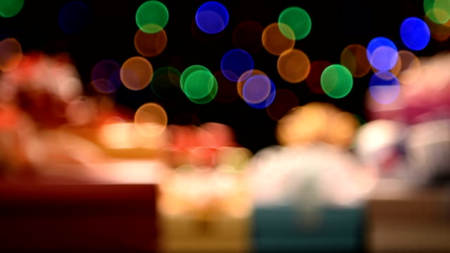 Rack focus christmas gifts with defocused spot lights on the background