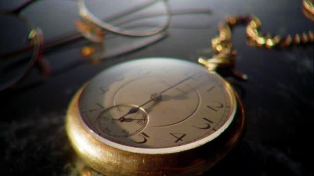 rack focus close up gold pocket watch and eyeglasses in background - 懐中時計点の映像素材/bロール